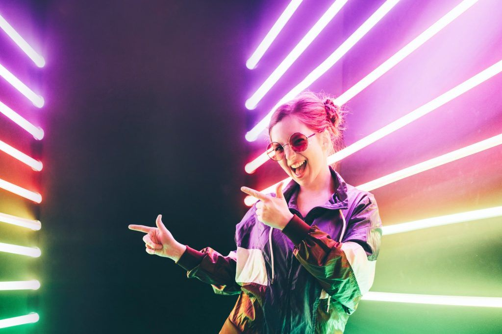 Cheerful cute girl pointing on copy space at neon background .