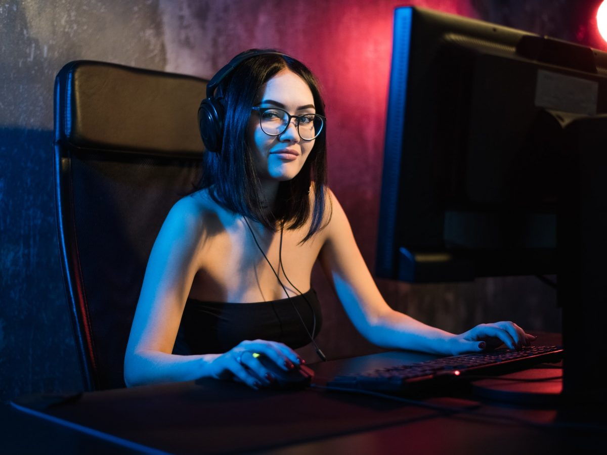 Portrait of the beautiful professional gamer girl playing in online video game, casual cute geek