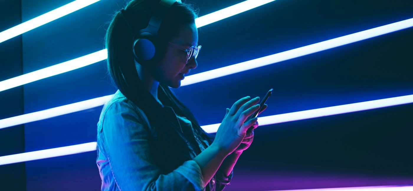 Woman in headphones listening music in neon light with phone on hands.